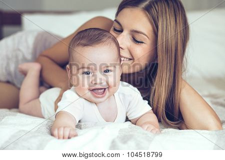 Portrait of beautiful mother playing with her 5 months old baby in the bed