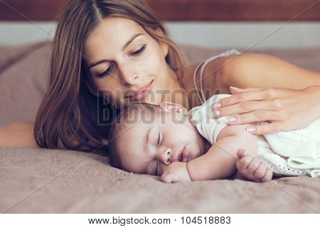 Portrait of beautiful mother with her 5 months old baby sleeping in the bed