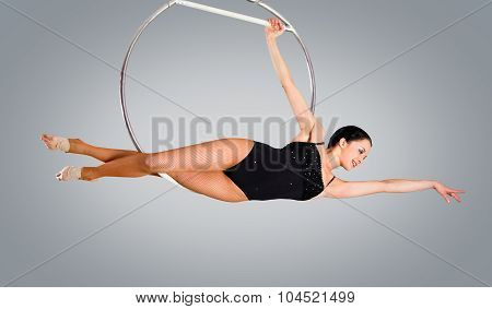 Plastic Beautiful Girl Gymnast On Acrobatic Circus Ring In Flesh-colored Suit. Aerial Ring