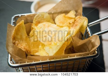 Deep fried chips served in a metallic fryer basket