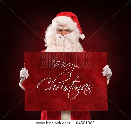 Santa Claus holding a red sign with