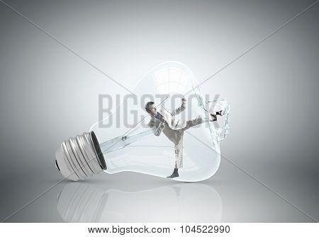 Businessman inside light bulb braking it to get out