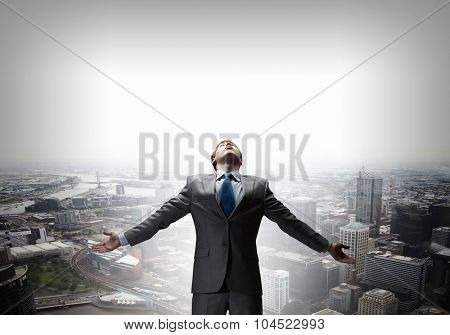 Confident businessman with hands spread apart on cityscape background