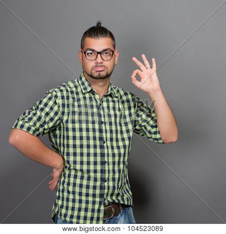 Fashionable hipster man giving okay sign in studio