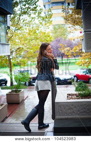 smiling beautiful  young woman speaking on smartphone wearing black jacket, shorts and black rubber boots, outdoor shot, rainy autmn day in the city