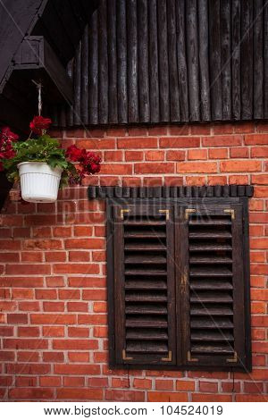 wooden window and pots with flowers on a mountain house