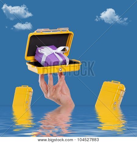 Hand holding a case with a gift in the water