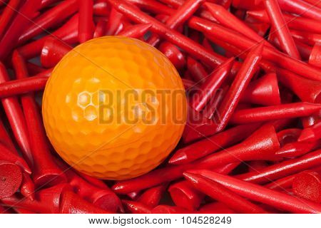 Orange Golf Ball Lying Between Wooden Tees