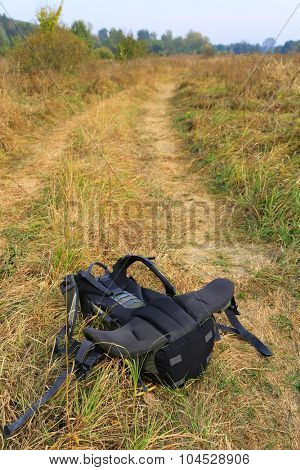 Tourist backpack on dry meadow grass