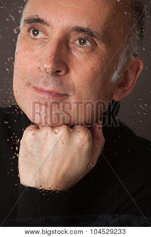 Handsome man looking through a wet window