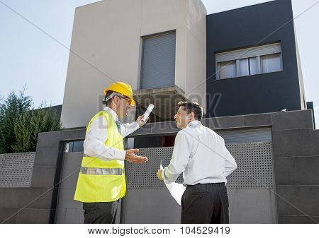 Customer And Constructor Foreman Worker Talking On New House Building Blueprints In Real State