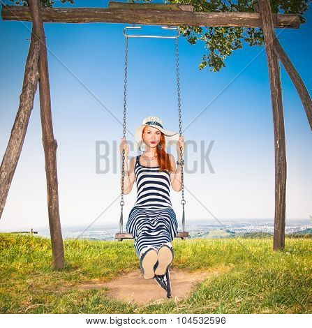 Beautiful girl on the swing under a tree with panoramic view on Vojvodina, Serbia.