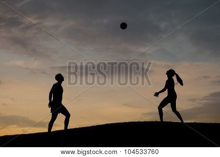 Boy and girl playing volleyball on the nature.