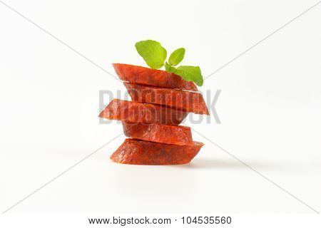 stack of pepperoni sausage slices on white background