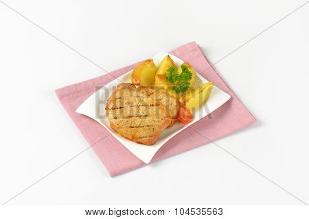 plate of grilled slices of pork and roasted potatoes on pink place mat