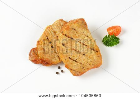 grilled slices of pork on white background