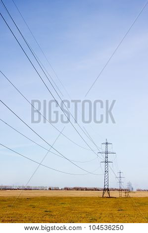 High Voltage Post. High-voltage Tower Sky Background. Power Lines In Field.