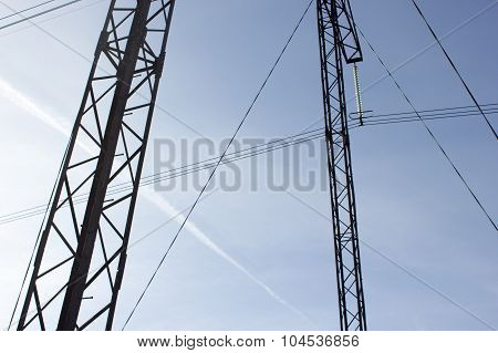 High Voltage Post. High-voltage Tower Sky Background. Power Lines Of Blue Sky At Sunny Autumn Day.