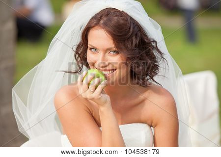Happy bride with an apple