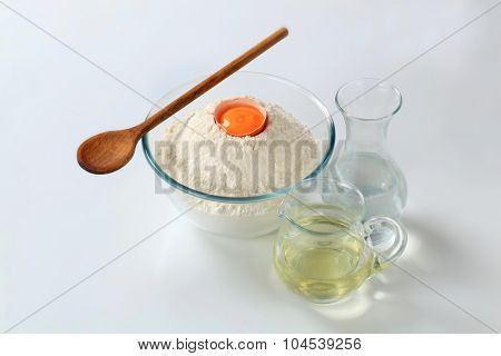 bowl of flour with yolk, carafe of water and jug of cooking oil