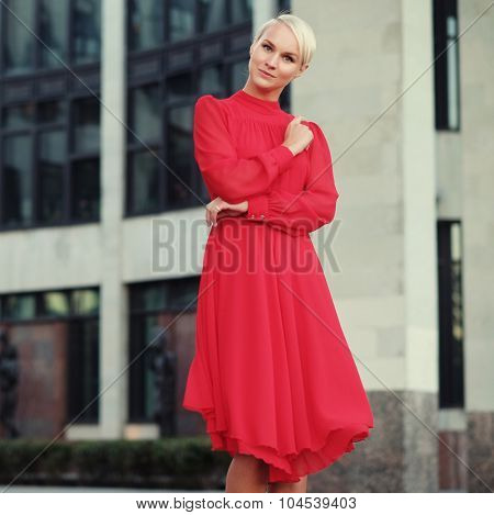 Happy beautiful woman in red summer dress walking and running joyful and cheerful smiling. Summer day.