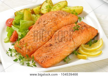 close up of pan fried salmon fillets served with vegetable garnish on white square plate