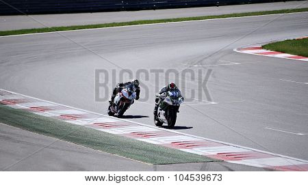 Two Racers On A Motorcycles Rides On The Speed Of The Track