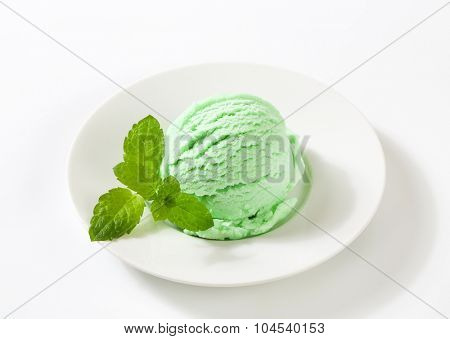 scoop of green ice cream on white plate