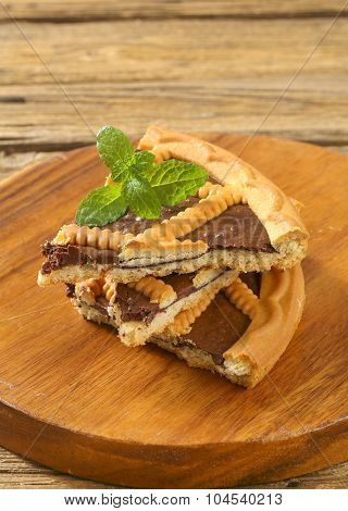 slices of chocolate tart with lattice top on round wooden cutting board