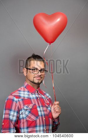 Handsome hipster man with red heart baloon in studio