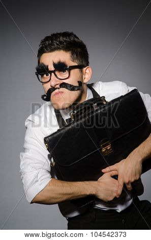 Young caucasian man with false moustache against gray