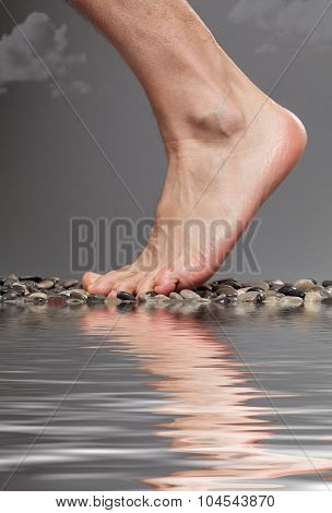 Close up of foot by the water on a stormy day