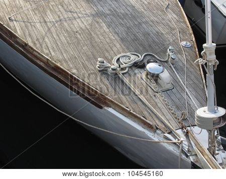 Prow Of Sailboat Moored In The Harbor With Wooden Deck In Foreground