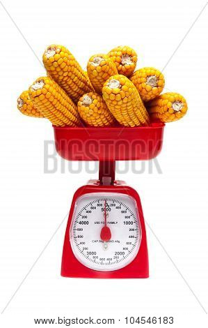Corn And Kitchen Scales On A White Background