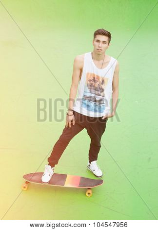 Young male skateboarder standing on longboard on a warm summer evening. Skateboard ramp. Warm color