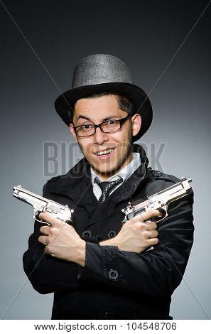 Criminal in black coat holding hadgun against gray