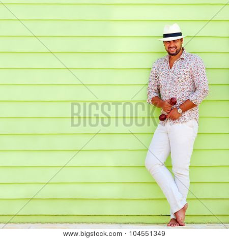 Happy Man With Maraca Playing Music Near The Colorful Wall