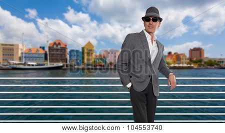 Fashionable man standing by a bridge in Curacao