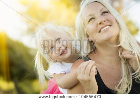 Pretty Mother and Little Girl Having Fun Together in the Grass.