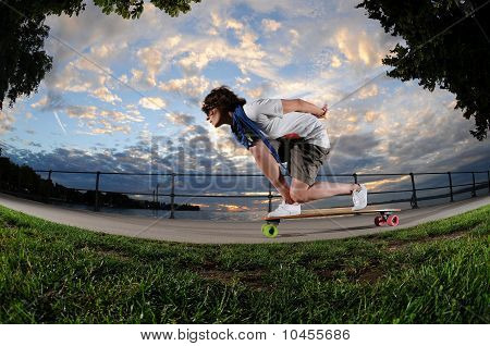 A portrait of a young woman riding on a longboard along sidewalk by the lake in AustriaA portrait of