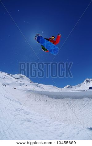 Jumping freestyle snowboarder in half-pipe on a sunny day
