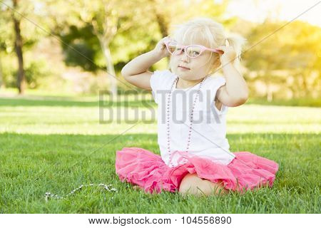 Cute Little Girl Playing Dress In The Grass Up With Pink Glasses and Beaded Necklace.