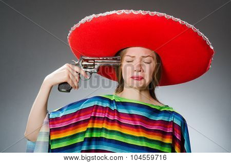 Girl in mexican vivid poncho holding handgun against gray