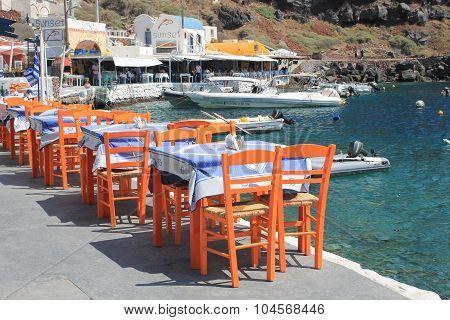 Greek Tavern With Orange Wooden Chairs By The Sea Coast, Greece, Santorini