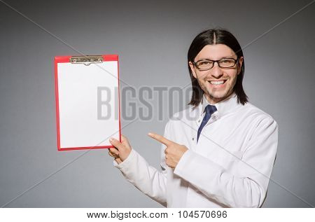 Male doctor with diary against gray