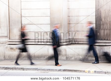 Blur of business people walking pass the Bank of England wall