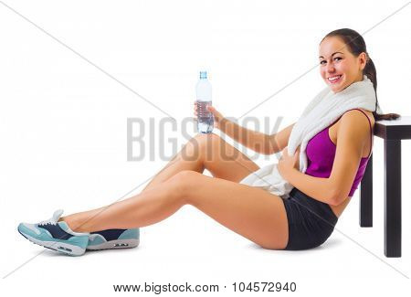 Young sporty woman with towel and water bottle isolated