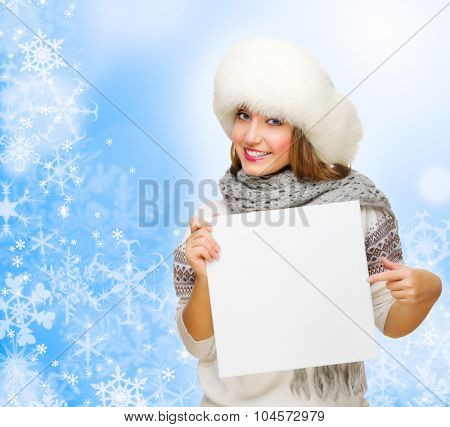 Young girl with empty card on blue winter background