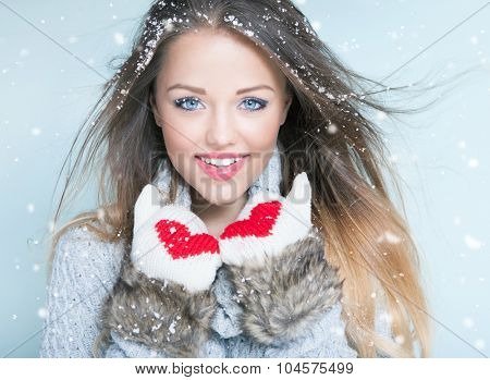 Face close up of beautiful happy young woman wearing winter gloves covered with snow flakes. Christmas snowing portrait concept.