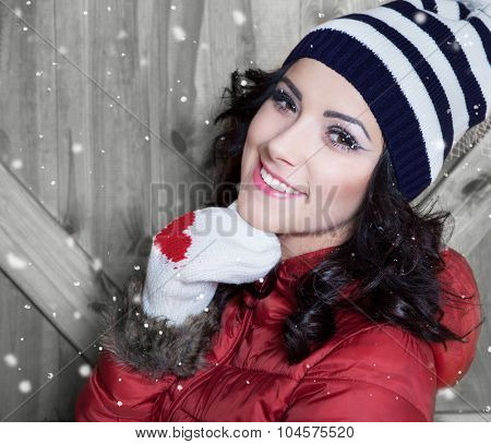Beautiful happy smiling young woman wearing winter hat and gloves covered with snow flakes. Christmas portrait concept.